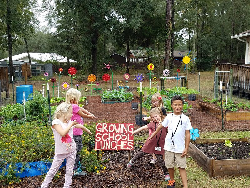 "Newberry Elementary School's garden with kids pointing to ""Growing for School Lunches"" sign"